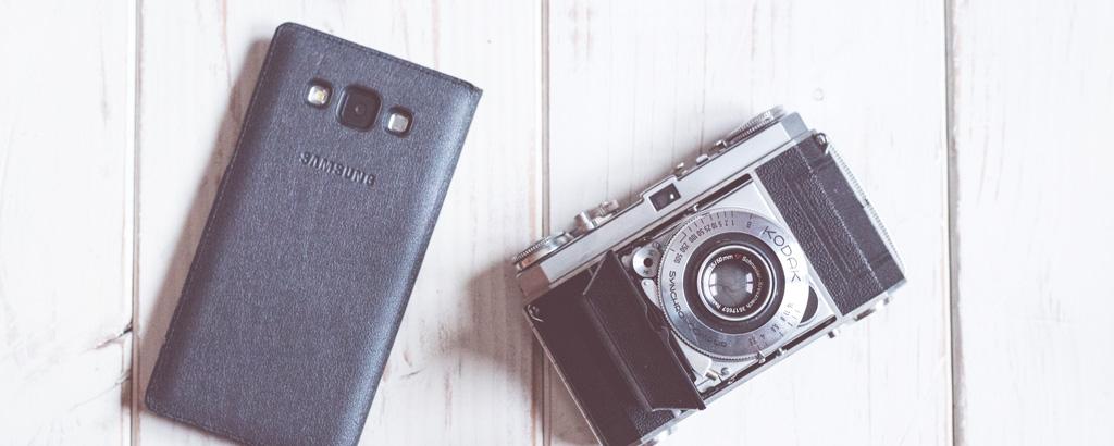 Smartphone neben Analogkamera